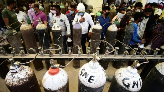 Des usagers attendent le remplissage de bouteilles d'oxygène à Allahabad (Inde), le 20 avril 2021.