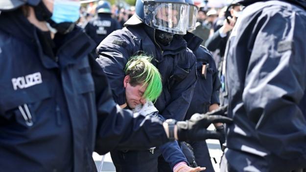 Des policiers allemands bloquent un manifestant opposé à un texte de loi renforçant les pouvoirs du gouvernement fédéral pour durcir la lutte contre le coronavirus, le 21 avril 2021 à Berlin