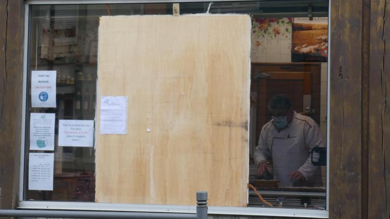 Une plaque de contreplaqué occulte en partie la vitrine endommagée de la boucherie, rue de Normandie.
