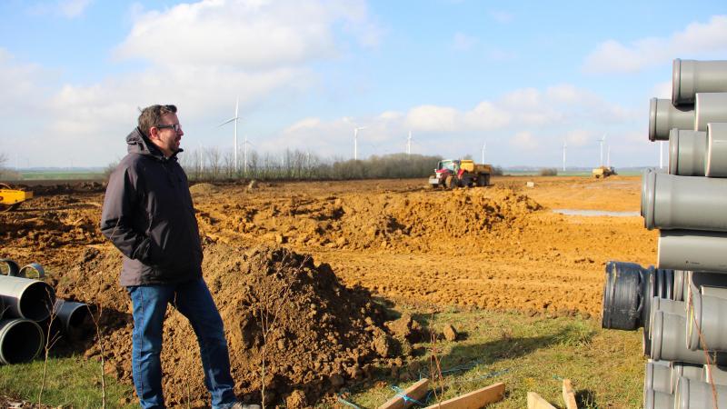 Sébastien Galland, l'un des trois porteurs du projet Picardia. En arrière plan, les ouvriers construisant l'entrepôt de 7000m² qui accueillera le complexe multisport à la ZAC de la mine d'or de Croixrault.