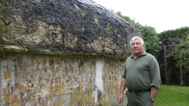 Jean-Luc Silvert devant le bunker qui occupe une grande partie du jardin situé devant sa maison, dans le centre de Méaulte.