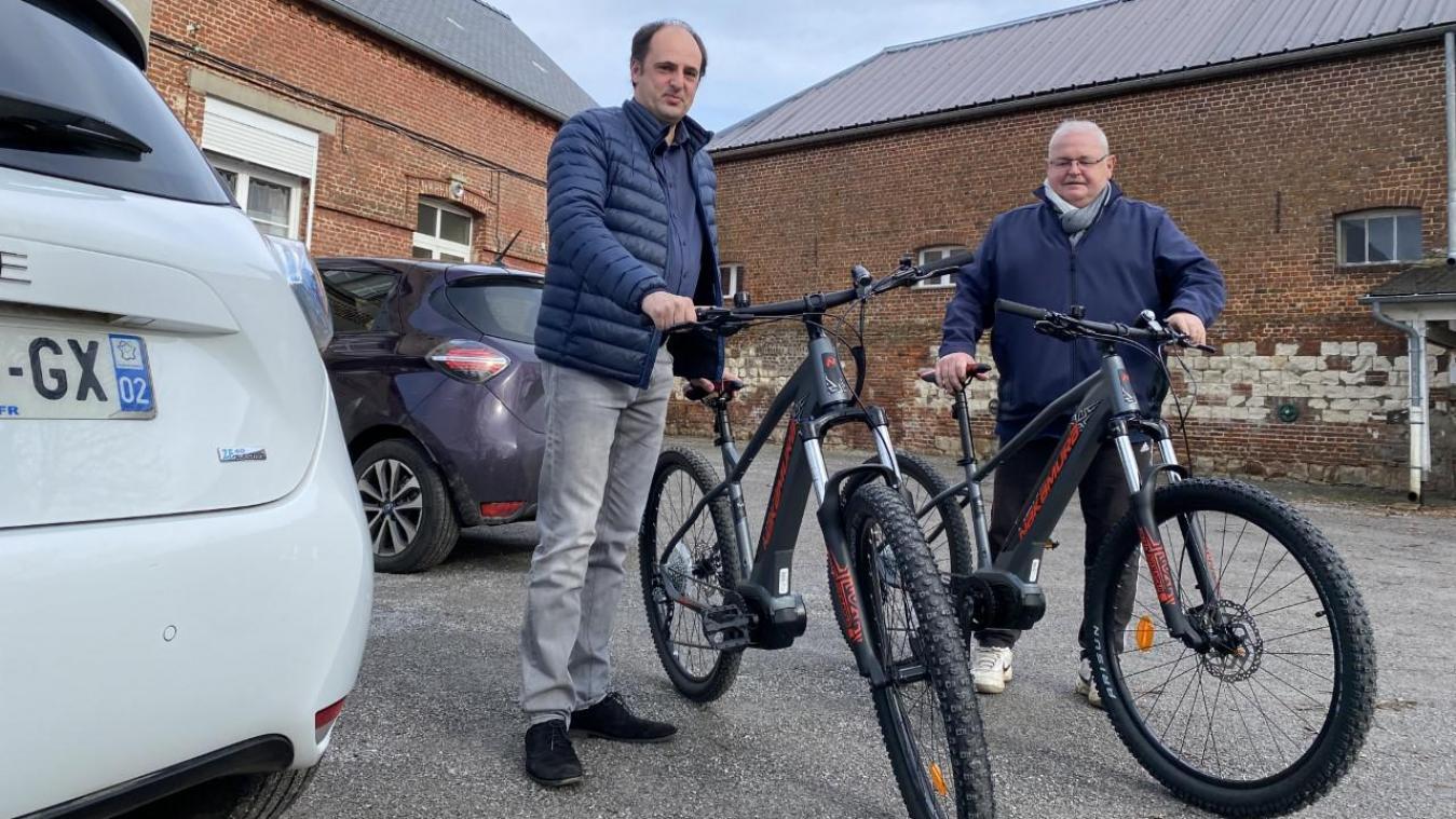 Le maire Christophe Parent et son adjoint Jean-Pierre Lecompte avec leurs voitures et les vélos électriques.