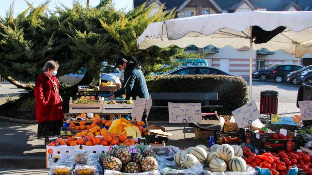 Une cliente achète ses fruits et légumes sur le marché de Conty samedi 27 février.