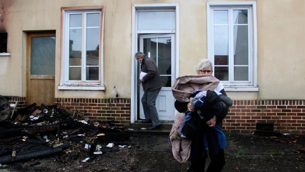 Patricia sort de chez elle avec un tas de vêtement. Le maire d'Aubigny, Georges Leclercq, ferme la porte. La maison a été ravagée dans un incendie dans la soirée du 10 mars.